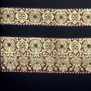 Square shawl with a green center and borders on all four sides. Borders have two wide and three narrow bands showing a conventionalized floral pattern in yellow, brown and green. Border woven separately and joined by sewing.