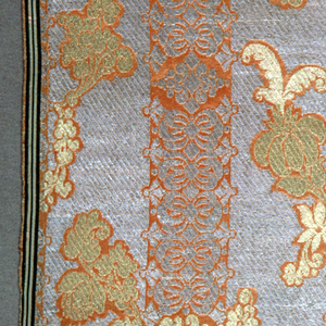 Light orange (salmon) satin ground with the design disposed in stripes of bow-knots in silver with a staggered repeat of a scrolling leaf and flower motif brocaded in gold across the stripes. Selvages of green and white stripes.