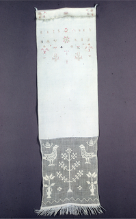 Towel cover ornamented at the top with name, sprays, and baskets of flowers, birds, trees, and stars in cross stitch. At the bottom, a band of drawnwork showing birds, crowns, and flowering stems in darning stitch. Fringe at top and bottom.