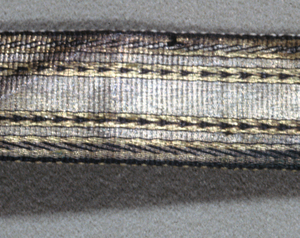 Yellow gold, light gold and black warps which form the pattern of vertical stripes, the center ones with chevrons in black, and the outer ones with diagonal pin stripes, also in black. The weft, which is concealed, consists of six linen threads.