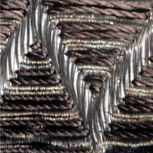 Gold and silk in a gun-metal color. The warp consists of thick threads of linen over which has been woven the gold weft as the background and a zigzag pattern. The space in between have been filled with floats of gun-metal colored silk warps.