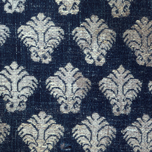 All-over pattern of small-scale, stylized floral forms brocaded in white silk and silver thread on a ground of blue satin.  Satin ground originally shot through with extra silver (flat metal strips) threads; now almost entirely worn away.