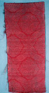 Deep red ground with pattern of large-scale ogive enclosing a central stylized rosette. Pattern produced by extra wefts of silver thread (flat metal strips) shot through the surface–when not needed for design pass to reverse of fabric--results in a damask-like effect.