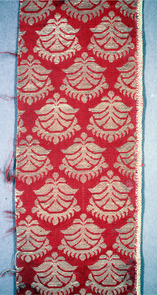 All-over pattern of stylized floral forms brocaded in tan and tinsel threads on a red satin ground.