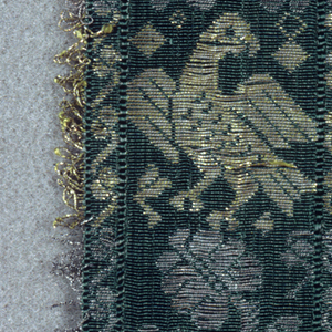 Design of bird with spread wings alternating with flowering spray; set between narrow borders and edged with picots in silver and gilt thread.