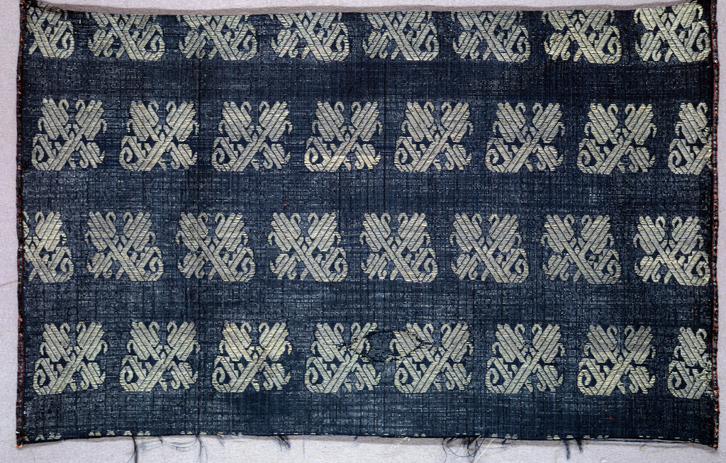 Ground fabric of dull blue plain cloth with extra wefts of silver thread shot through in alternate weft rows. Small scale pattern pf stylized floral forms, arranged in horizontal rows, brocaded in silver gilt.