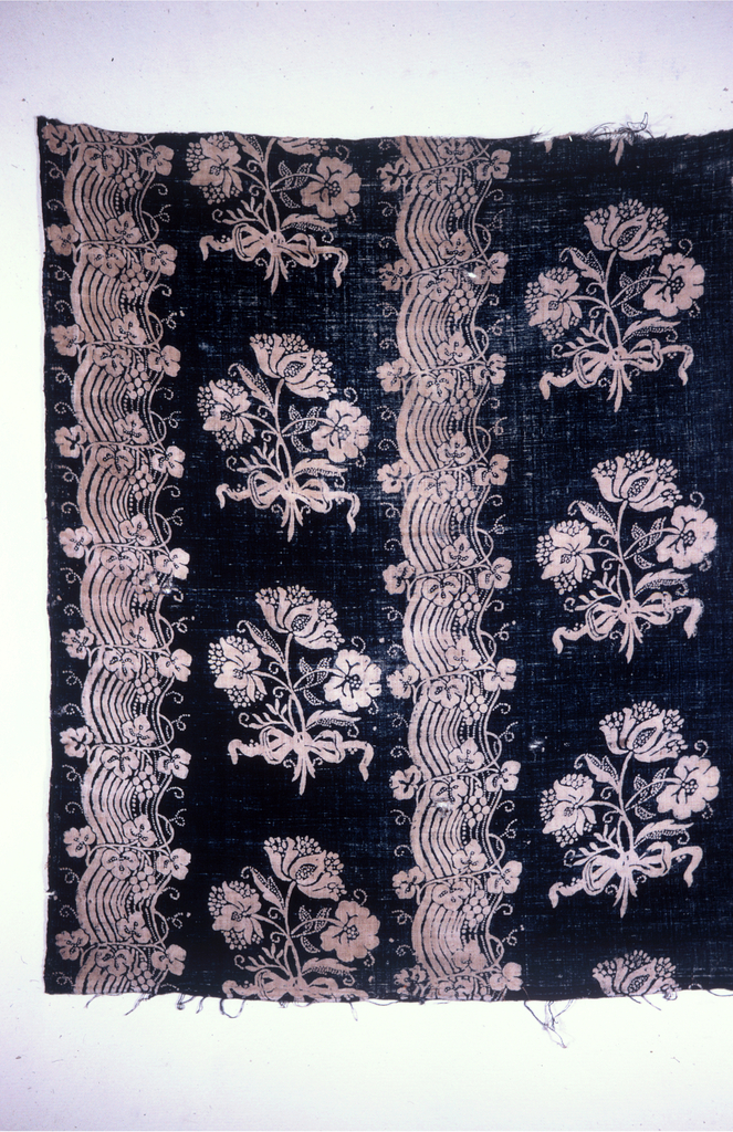 Bedcover patterned with cutwork in a chevron design and edged with insertion and a border of bobbin lace.