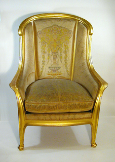 """This upholstered armchair has closed arms and a separate seat cushion.  The armchair's contour-edged and gilded frame is arched and has a curved back rail with down-turned """"ears.""""  The chair's outcurving arms flow into its front legs, terminating in pointed feet on supports.  The chair's rear legs are square, slightly outcurved, and moulded on their outer surface.  Upholstery is a multicolor pastel silk needlepoint on ivory ground, depicting a vase, round flowers, vines and leaves."""