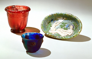 Thick walled oval dish of glass paste: predominantly blue-green background on top surface with reclining nude woman and nude child with large white bird among green plants, two with blue flowers.  Bottom and outer wall are of white glass paste in which color is randomly imbedded.