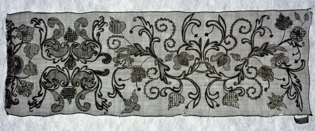 Strip of white linen embroidered in white linen in design of conventionalized flowers and leaves with scrolls.