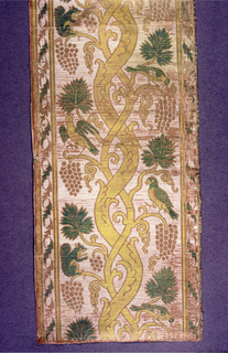 Border with a grapevine motif. Birds and squirrels sit on branches, some appear to be eating grapes.