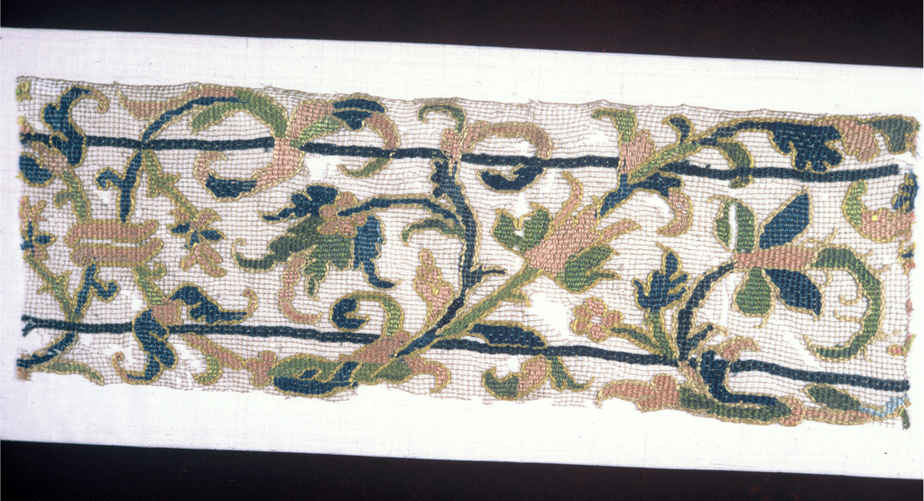Design of scrolling stem with leaves and flowers in pink, blue, green and yellow silk.