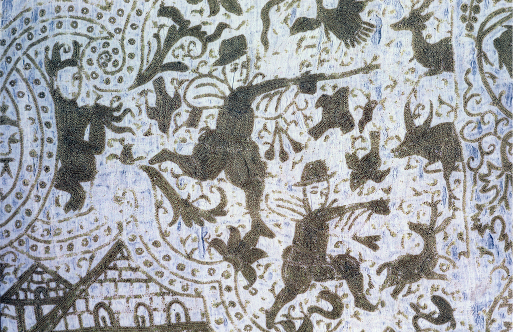 Rectangular linen coverlet embroidered in yellowish silk on an off-white ground. Eight cartouches showing a mixture of European and Indian figures of hunters on horseback and on foot, with exotic animals and vegetation. Devil-like figures with horns appear throughout. The bottom vignettes contain scenes from the biblical story in which Judith severs Holoferne's head to save her people. Figures fill all of the space inside and outside the scrolling framework of the cartouches.