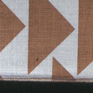 Varying size triangles, all facing one direction and randomly placed to form a pattern. Tan triangles printed on white.