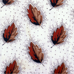 Square sample with a tiny design of oak leaves—half red, half brown—surrounded by a dark brown stipple pattern on an off-white ground.