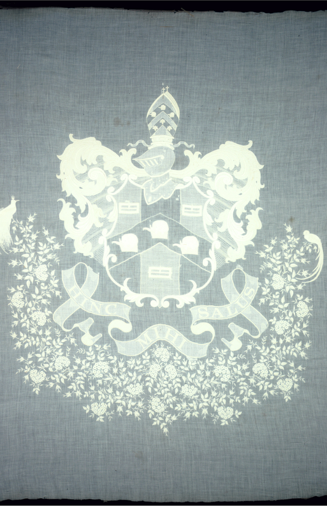 "White-on-white embroidered design of a shield showing three square buckles and three elepants heads on a chevron. Above the shield are a helmut, a mitre with three elephant heads and two crosses. Mantling of leaf scrolls. Below are rose plants and flowers resembling geraniums with a bird at either side. Motto is ""Hinc Mihi Salvus"" or ""Hence My Salvation."""