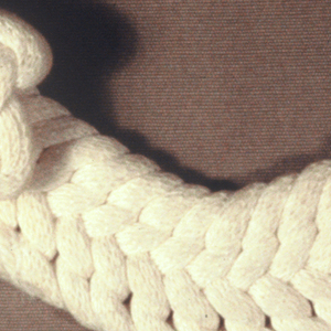 Cream knitted object in curved form.