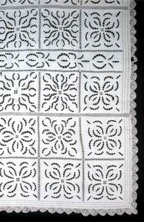 Large table cover with a design arranged in squares of conventionalized four-leafed flowers, done in open cutwork. Border is drawn work and edged with lace.