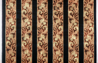 Runner with vertical stripes of dark blue cut pile that alternate with tan satin stripes together with a stylized interlocking floral design of vaguely Persian inspiration in dark rust and light tan cut and uncut pile. Plain weave selvages on long sides and twisted metallic fringe on a metal thread heading at the ends.