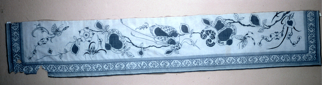 Valance or border in heavy white cotton embroidered in blue cotton with a main design of a crow in flight appearing between two sprays of fruit-bearing branches. Flowers, butterflies and bats in a detached design. Border has stylized plants in fret.