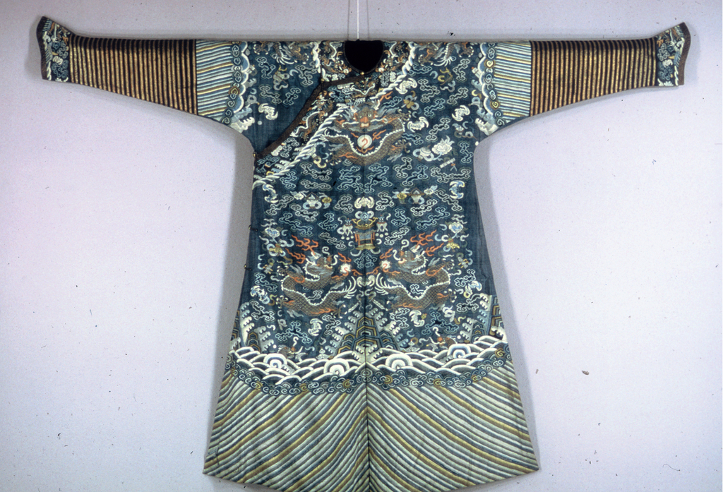 Robe with rounded neckline, diagonal closure across right shoulder, slits at center front and back hem, and horseshoe-shaped sleeve cuffs.Twelve-symbol robe with ultramarine ground with deep wave border of diagonal stripes, clouds, gold dragons, and many other symbols all over. Blue and gold striped sleeves. Lined with pale blue silk damask.