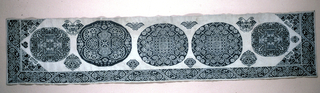 Valance or border in heavy white cotton embroidered in dark blue cotton in a design of five large detached roundels containing highly stylized plants and animals. Border has a design of stylized flowers.