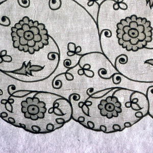Straight panels intended for sleeves with a small appliquéd and embroidered floral design. A wide border shows a  vine pattern along with a flower and vine pattern of appliqué pina outlined in white embroidery.