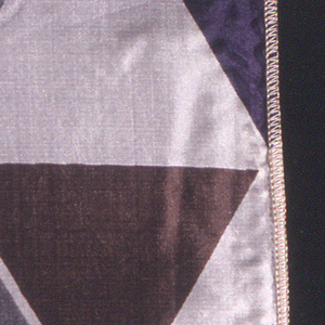 Rows of triangles printed in grey, purple and brown on white. Serged on two sides, cut on two sides.
