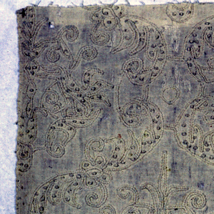 Fragment of a wide border of white linen embroidered in white in a design showing a symmetrical, ogival pattern with conventionalized floral motifs. Couching stitches produce a cable-like effect. Knots symmetrically placed to form part of the design.