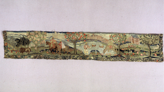 Horizontal landscape panel with lion under trees, horseback riders, pool and fishermen, and so forth. Fruit trees spaced across foreground and architecture in background. Stylized floral border with black outlines on all but top side. Work needlepoint with torches of silk: red, yellow, blue, green, brown, grey, and lavender.