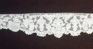 Long border or collar, straight on one edge and scalloped on the other, shaped with a wide central section that narrows out on the ends. Point d'Argentan style in a rich design with a great variety of stitches. A conventionalized vase form alternates with rich floral motifs. Hexagonal ground.