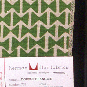 Rows of two triangles facing each other forming a bow tie shape, with alternating rows of off-set repeat. Printed in green on natural.