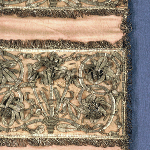 Wall pocket with three pockets of rose silk, decorated with metal trimming laid on in high relief in symmetrical designs. Trimmed with looped fringe.