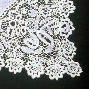 Handkerchief trimmed with Belgian style lace showing Honiton motifs, floral sprays connected by a large square réseau.