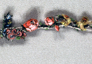 Buds and flowers made of ribbons and silk floss fastened closely to linen cord.