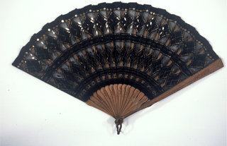 Pleated fan. Metallic net leaf backed with black chiffon. Obverse: decorated with bands and diamonds of black sequins and paillettes sewn on taffeta as well as metal net. Carved sandalwood and pierced sticks.