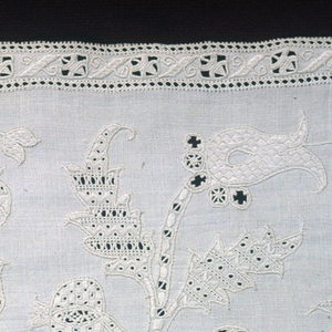 Band or border of white linen with elaborate, symmetrically arranged design of vine and flowers, in cut work, drawn work and embroidery.