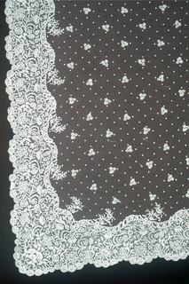 White lace shawl of fine mesh with detached floral designs and a wide floral border.