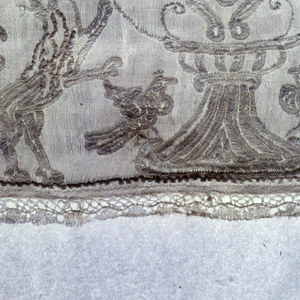 Border for an alb. Very sheer white cotton; embroidered in white cotton. Design symmetrically arranged, of delicate flowering vine, originating in an urn; below dogs and lions rampant, above birds. Second motif: shield with figure of a child on a wheel. Above shield, helmet with closed visor.