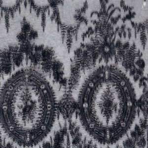 Piece of a flounce in black silk Chantilly style bobbin lace. Pattern of medallions and architectural details interspersed by floral sprays.