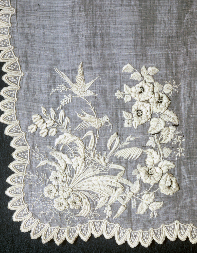 Elaborately embroidered handkerchief of fine white linen. Corner design worked in naturalistic flower spray, bird's nest with baby birds, and a pair of adult birds with overhanging flower clusters. Latter are worked with raised separate flower petals, possibly made and attached separately. With openwork and buttonhole details in centers. Adult birds have raised wings. Partly free from ground and probably made separately. Edge is scalloped and worked in a kind of lambrequin design.