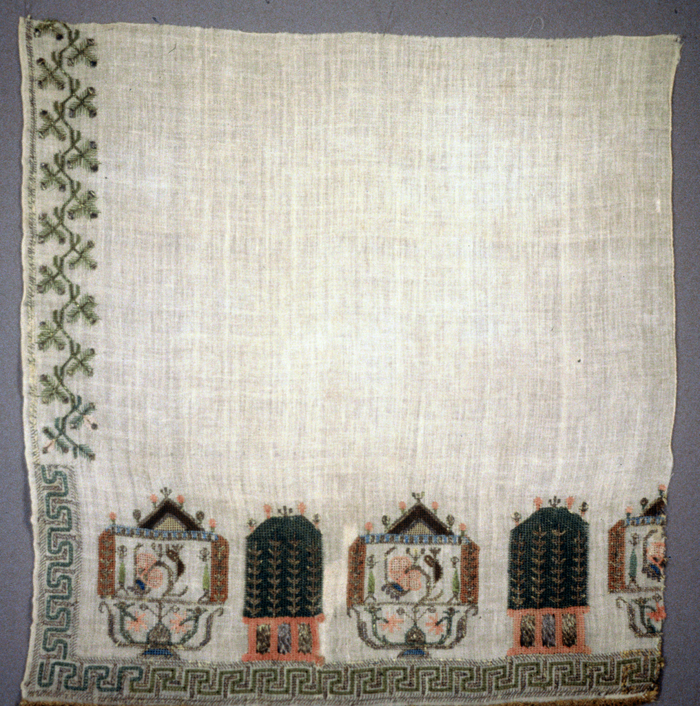 End crossed by two types of shrine forms (?) alternating in blue, green and pink silk silver thread with touches of brown and cream. Fret border in cream and silver across the bottom and short distance up the sides with stylized floral boarder above this. Much ribbed silver braid across end.