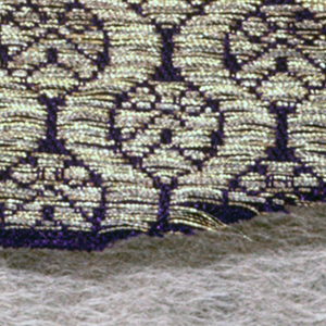 Small-scale all over design of symmetrical stylized leaf repeats in frame-work of continuous spiral bands, in bright gold on deep purple ground. Wide twill selvage set off by two stripes formed by metal floats, one stripe with cotton cord under floats.