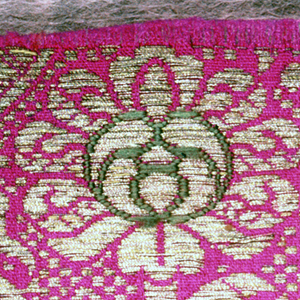 Tight arrangement of medium-scale stylized curving flower sprays and surrounding diaper pattern in gold on a bright magenta ground. Flower heads accented with blue and green.