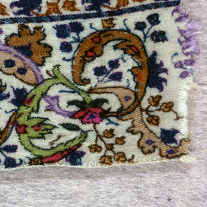 Kashmir shawl fragment. Horizontal repeats of symmetrical vase and flowers flanked by large elaborate interlace of decorated arabesques; twining flowering sprays fill interstices; scrolling floral guard band at bottom with decorated guard stripes above and below. In bright turquoise, greens, purples, browns, cerises on pale tan ground.