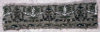 Horizontal band with symmetrical repeats of tri-partite sawtooth leaves and smaller green leaves alternating with flowering spray wreathed with small leaves. In beige, tan and greens with outlines of dark brown on a khaki-colored ground. Floral guard band at bottom with decorated guard strips. One plain twilled selvedge.