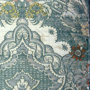 Silk fragment showing detailed pattern in silvery shades of green and off-white with touches of salmon pink and yellow. Design has a symmetrical motif in two variants with a vertical bunch of flowers surmounted by fanning leaves surmounted by decorated pear-shaped cartouche with diaper filling, in a close-set medium sale diagonal repeat giving allover effect.