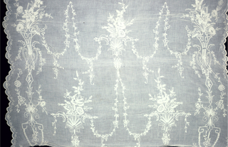 Part of a white muslin curtain embroidered in white. Design has a repeating pattern of vases with flowers connected by garlands. Both edges scalloped.