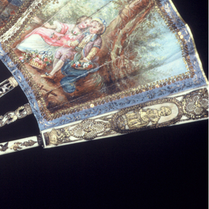 Pleated fan. Gilded parchment leaf painted with gouache and embroidered with sequins. Obverse: figures in 18th-century dress divided into three panels. Reverse: three panels, each enclosing a spray of flowers. Carved and pierced ivory sticks overlaid with gold foil. Pin is set with a faceted blue gem.