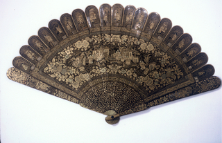 Brisé fan. Black and gold lacquered wood sticks. Delicate, all-over decoration encloses a panel depicting a garden scene with figure groups. Ends of sticks decorated with different vignettes of figures and foliage. Details in red. Guards decorated with ground of flower and lantern forms, and vignettes of figures.